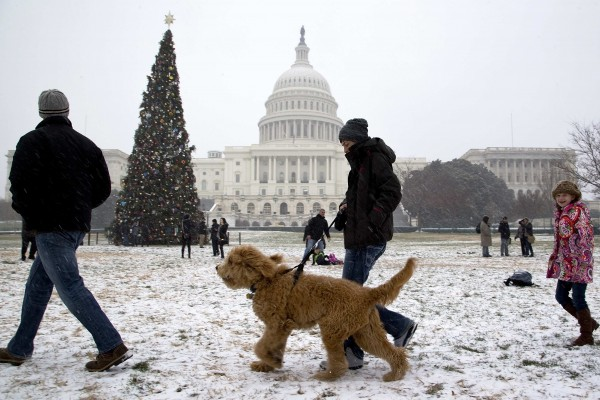 People walk in light snow flurries at the U.S. Capitol in Washington, Dec. 8, 2013.