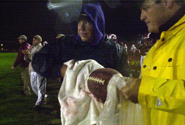 Ed Hackett (right) prepares to hand a dry football to Bobby MacDonald during Bangor's 3-0 win over Lewiston in September 2002 at Cameron Stadium in Bangor.