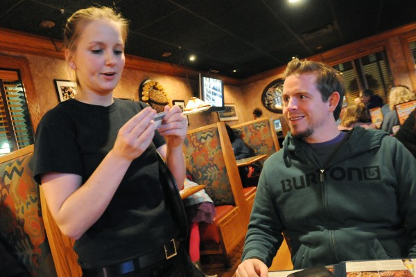 Waitress Sarah Bolton checks the identification of Seth Collins after he ordered a beer at the Ground Round in Bangor on Saturday night. Collins, from Kentucky, has been traveling the country giving $500 dollar tips to waitresses and waiters. Collins had no plans of tipping $500 on Sunday. He plans to offer that tip elsewhere in Maine on Monday.
