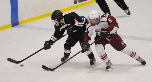 Brewer High School's Gabriel Valley (left) and Bangor High School's Nick Graham battle for the puck during the game at Sawyer Arena in Bangor Tuesday evening.