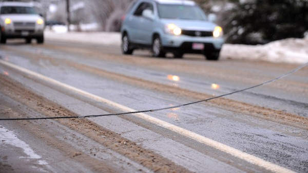 Cars drive around a utility line that was hanging very close to the road on North Main Street in Brewer Monday. Power outages were reported in several communities due to the ice storm.