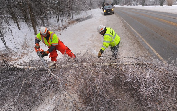 Maine DOT workers James Johnson Sr. (left) and Richard W. Doucet work on clearing trees from the roadway along Route 178 in Eddington Monday afternoon. The trees were so heavily crusted over with ice that they were leaning over the road and had to be cut down.
