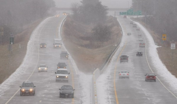 Traffic along I-95 in Bangor moves swiftly as snow starts to fall on Monday.
