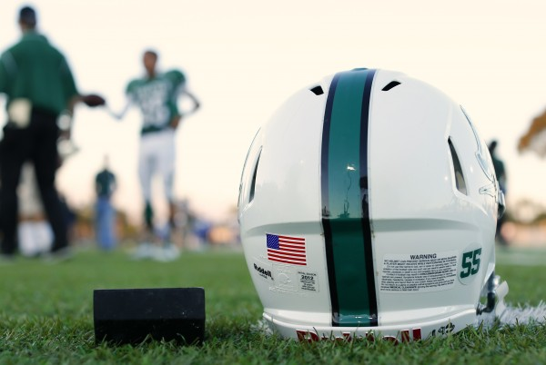 A football helmet's health warning sticker is pictured between a U.S. flag and the number 55, in memory of former student and NFL player Junior Seau, as the Oceanside Pirates high school football team prepares for their Friday night game in Oceanside, California September 14, 2012.