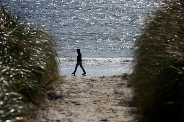 A woman walks on the beach at Pine Point in Scarborough Thursday Oct. 11, 2012.