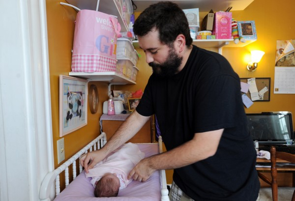 Matt Nichols adjusts his two-week-old daughter, Ruby's, blanket as she sleeps. Nichols' wife, Heather, 29, passed away on August 8, 2013, at Eastern Maine Medical Center from necrotizing fasciitis, a flesh eating bacteria, that she contracted from an episiotomy during childbirth.