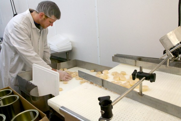 Adam Callen packs scallops into cans outfitted with a date and temperature indicators at Bristol Seafood on Portland's waterfront on Wednesday. The company recently got a cash infusion from a Silicon Valley investor.