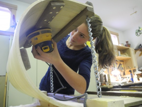 Abby Chamberlin, 15, of Camden, uses a power sander to meticulously smooth the toboggan she and three friends have been working on for six weeks. They will race in the upcoming 24th annual U.S. National Toboggan Championships at the Camden Snow Bowl.