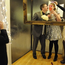 Adam Swenson applies a fake mustache as Courtney Smith holds a crown over her sister Ambrosia Bertenshaw's head while she poses with her new husband Ben Noyes. Ben described the wedding on Tuesday as a New Year's Eve party where two people will get married. The couple will reside in Hampden.