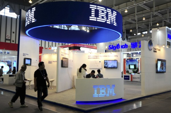 Visitors walk past the IBM booth at the 9th China International Software Product and Information Service Expo in Nanjing, Jiangsu province September 6, 2013. Battling a perfect storm of government suspicion and pricing probes in China, U.S. technology companies are having to re-think how they sell hardware and services in the world's second-biggest economy. U.S. multinationals, including IBM, Cisco Systems and Qualcomm, are looking to settle price-gouging investigations and restore trust with Chinese regulators in the wake of reports that U.S. government agencies directly collect data and tap networks of the biggest domestic technology companies.