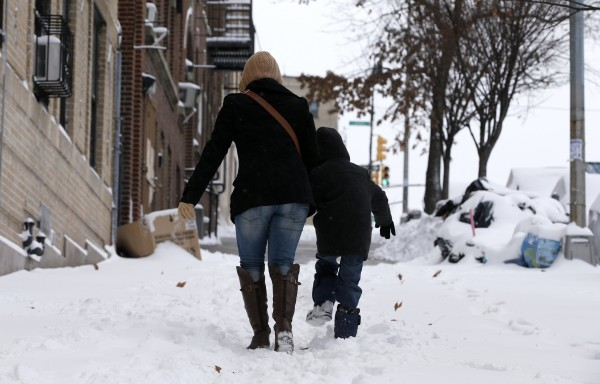 A woman and her son make their way up a snow covered sidewalk in the South Bronx section of New York City, January 3, 2014.