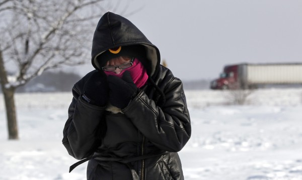 Megan Draper of Noblesville, Indiana covers her face to stay warm after stopping at a rest stop on Interstate 65 north of Indianapolis, Indiana January 6, 2014. A blast of Arctic air gripped the vast middle of the United States on Monday, bringing the coldest temperatures felt in two decades, causing at least four deaths, forcing businesses and schools to close and canceling thousands of flights. The polar vortex, the coldest air in the Northern hemisphere that hovers over the polar region in winter but can be pushed south, was moving toward the East Coast where temperatures were expected to fall into Tuesday.