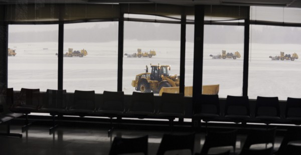 Snow removal equipment clears snow from the tarmac at Bangor International Airport in Bangor, Maine December 22, 2013.