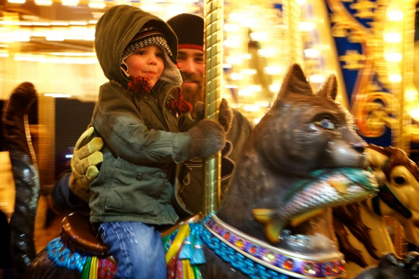 Laeton Michaud, 3, rides the Palace Playland carousel with his father Tyler at Old Orchard Beach on Tuesday night. The classic ride is normally closed in winter but  was open for a New Year's Eve community party sponsored by OOB365, a group that promotes the resort town all year.
