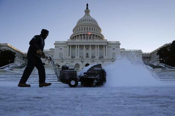 A worker clears snow from a walkway on the west front of the U.S. Capitol in Washington, January 22, 2014.