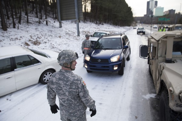 Georgia National Guardsman Command Sgt. Maj. Buddy Grisham is joined by fellow troops as they help people get their stranded cars out of the snow in Atlanta, Georgia January 29, 2014.  A rare ice storm turned Atlanta into a slippery mess on Wednesday, stranding thousands for hours on frozen roadways and raising questions about how city leaders prepared for and handled the cold snap that slammed the South.