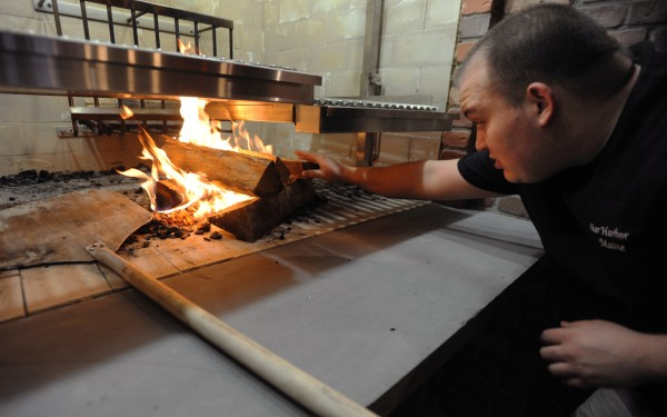 Grill Chef Jeff Russell lights a wood fire in the grill as Blaze, Bangor's newest restaurant, plans a soft opening for Tuesday with a grand opening on Friday.