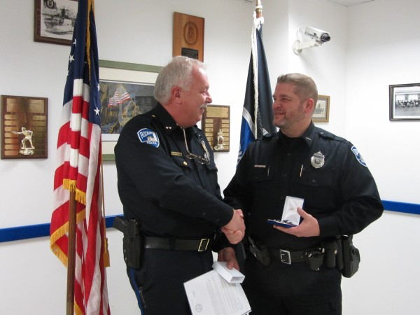 Rockland police Officer Joel Neal (right) was honored Wednesday for his bravery in disarming an armed man who wanted to commit &quotsuicide by cop.&quot Chief Bruce Boucher presented him with a medal at the city police station.