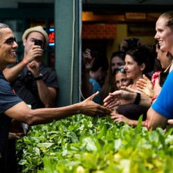 U.S. President Barack Obama greets peopel outside of the Island Snow shaved ice stand in Kailua Beach, Hawaii, on Dec. 31, 2013.