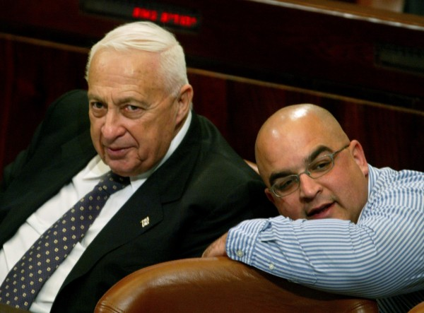 Israel's Prime Minister Ariel Sharon (left) and his son, parliament member Omri, attend a session of parliament in Jerusalem in this Nov. 10, 2004, file photo. Ariel Sharon died Saturday at the age of 85.