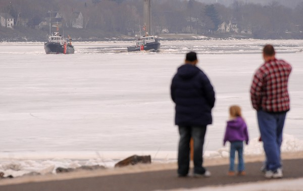 People watch as U.S. Coast Guard cutters Tackle (left) and Bridle break ice on the Penobscot River in Bangor on Saturday.