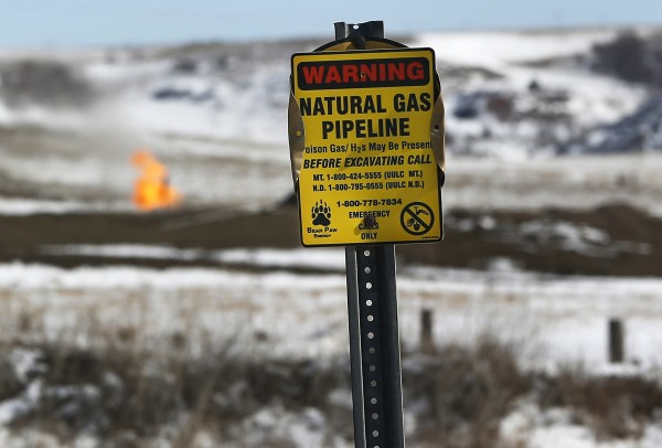 A warning sign for a natural gas pipeline is seen at an oil pump site outside of Williston, N.D.