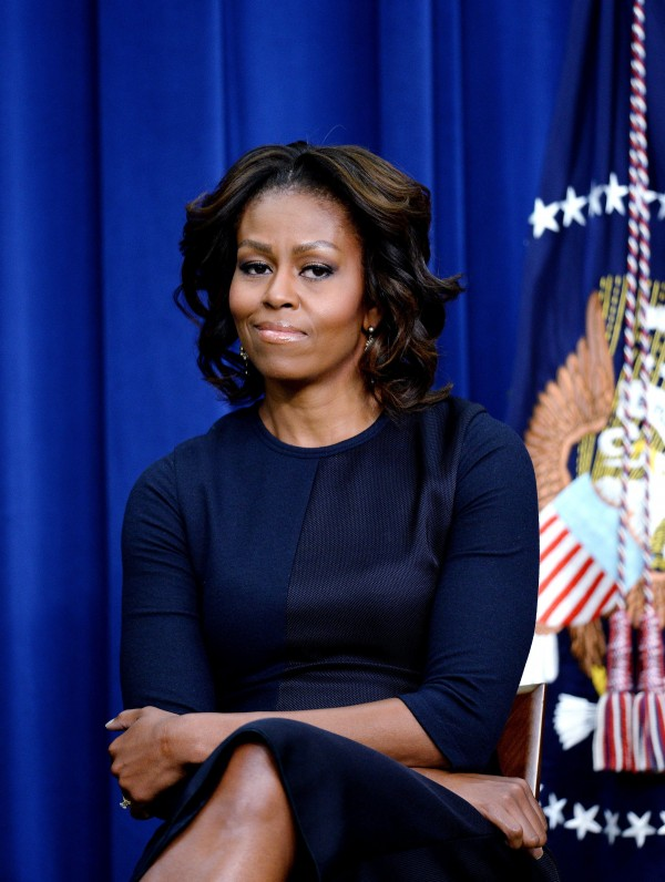First lady Michelle Obama listens as President Barack Obama speaks at an event on expanding college opportunity in the South Court Auditorium of the Eisenhower Executive Office Building, next to the White House, on Thursday. The first lady celebrated her 50th birthday on Friday.