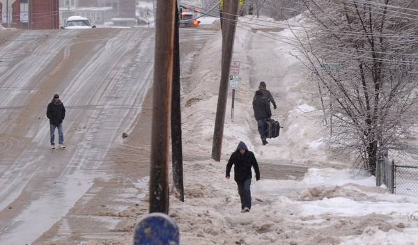 People walk along Union Street in the freezing rain on Dec. 22, 2013.