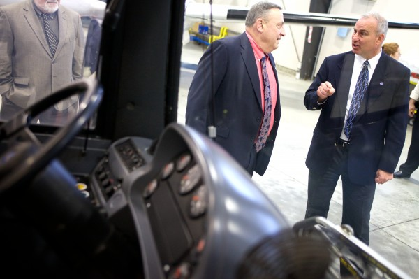 Hugh Corbett, executive director of the Maine Military Authority, shows Gov. Paul LePage a fixed-route transit bus refurbished by the company on Thursday in Augusta. The bus will soon go back into service in southern Maine.