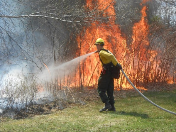 A Maine Forest Ranger uses a fire hose to douse a fire with high flame lengths earlier this year. He is wearing all of the protective gear issued to a Maine Forest Ranger, including Nomex fire-resistant pants and shirt, leather boots and gloves, a hard hat, eye protection, a portable radio and a backpack containing a fire shelter.