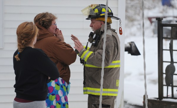 Phillipa Gilmore (center) talks with Lt. Frank Coombs about the fire in the house at 40 Main Road South in Hampden where she escaped along with her 13-year-old daughter on Monday afternoon. Listening in is neighbor Allyson Mitchell (left). A pet guinea pig was saved, but an exotic bird did not survive and a cat is still missing.