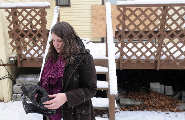 Tachia Barlow holds a charred dog sweater that belonged to one of her two dogs that were lost in a fire at her rented Dillingham Street home last Friday.