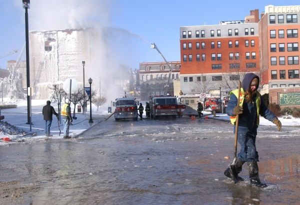 Bangor Public Works employees help ease the flow of water along Water Street as firefighters pump up to 6,000 gallons a minute onto the Masonic Hall on Main Street.
