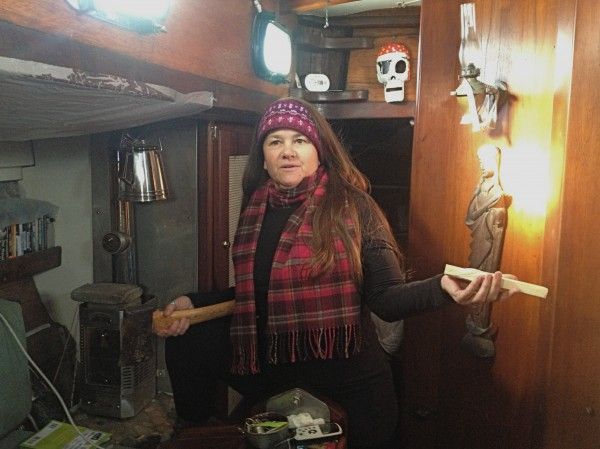 Maggie Morgan readies wood for her wood-burning stove on her floating 60 square-foot home, the cutter Viking.