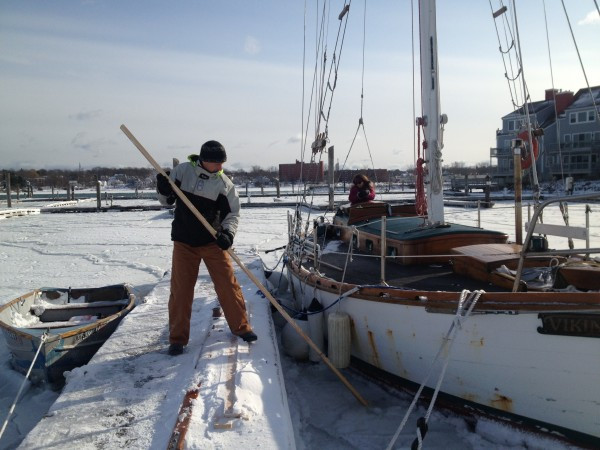 Richard Morgan chops ice from his home, the cutter Viking.