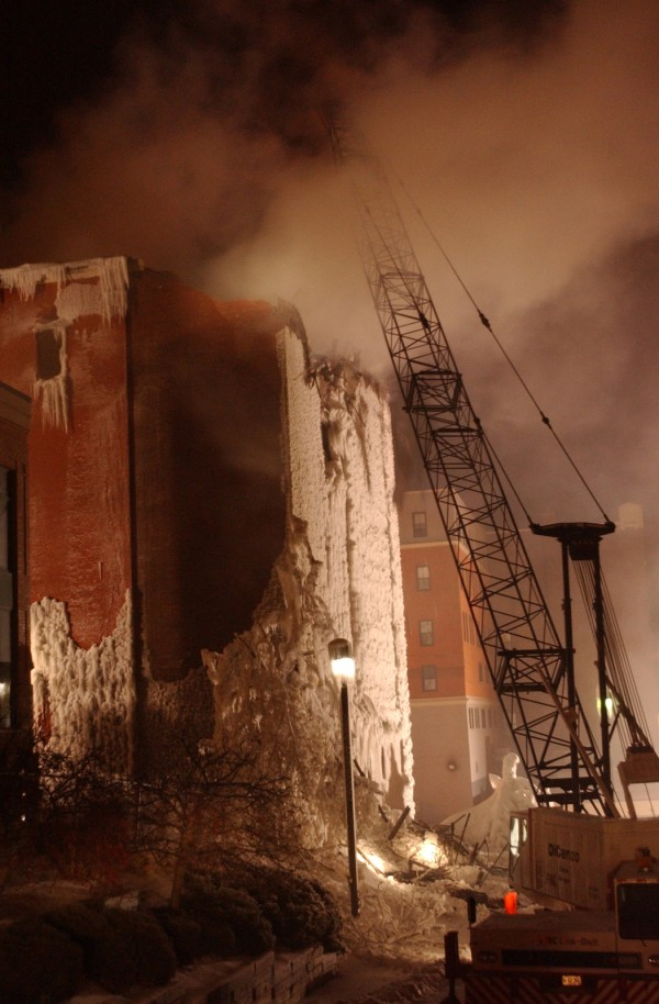 A crane begins to knock down the rear of the fourth floor of the Masonic Hall as night falls a day after the fire.