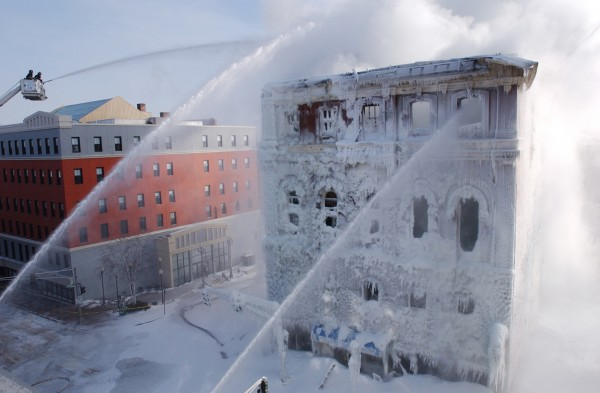 Fire crews from Bangor, Brewer and Orono battle the stubborn fire at the former Masonic Block on Main Street in Bangor in this January 16, 2004 photo. Crews began to tear down the building later in the evening to prevent an uncontrolled collapse of the unstable structure.