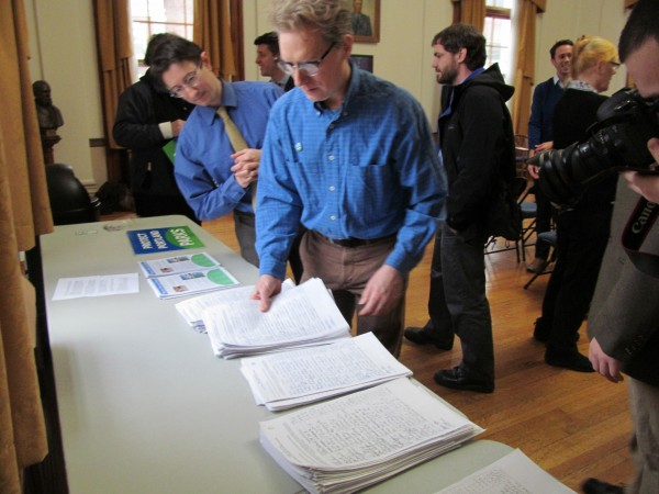 Attorney Rob Levin, left, and Friends of Congress Square Park President Frank Turek look over stacks of petition paperwork they say includes more than 4,250 signatures of Portlanders seeking greater protections against the sales of public space to private developers. The city agreed to sell 9,500 square feet of Congress Square Park to a hotel developer in September.