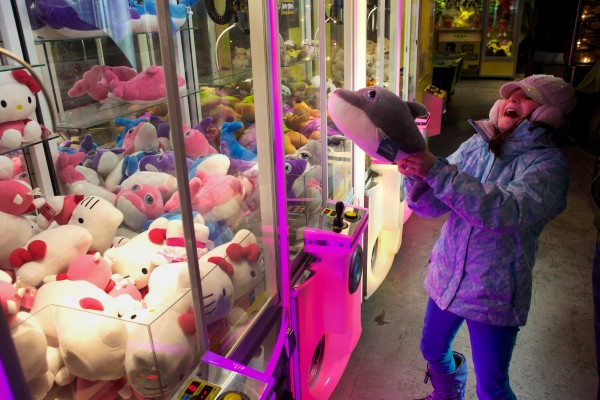 Ella Spencer, 10, of Milford, N.H., celebrates on her fourth attempt to get a dolphin toy out of a game in the Palace Playland arcade in Old Orchard Beach Tuesday night. The arcade is usually closed in winter but was open for New Year's Eve as part of a community beach party that included fireworks.