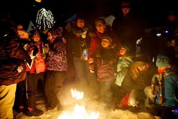 Children and adults roast marshmallows around a small fire in Old Orchard Beach on New Year's Eve.