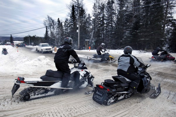 A group of snowmobilers cross a road during the Snodeo, Saturday, Jan. 21, 2012, in Rangeley, Maine.