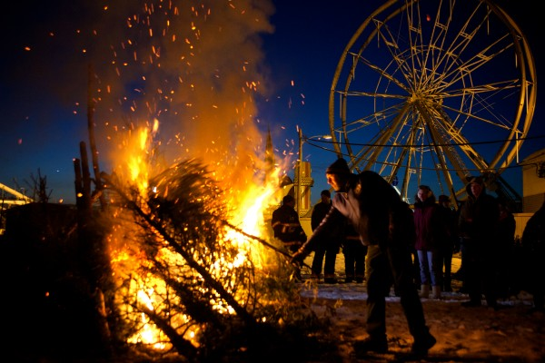 Tom Jones tosses another Christmas tree on the bonfire at a New Year's Eve celebration in Old Orchard Beach Tuesday night. Community and business group OOB365 sponsored the event which was free and included fireworks.