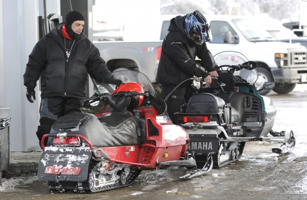 Mike Billings and Adam Somes, both of Eddington, fuel up their snow sleds at G and M Variety Market in Holden on Wednesday.