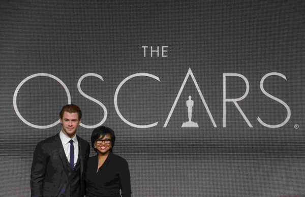 Actor Chris Hemsworth, left, and Academy of Motion Picture Arts and Sciences President Cheryl Boone Isaacs pose for photographers after the 86th Academy Awards nominee announcements in Beverly Hills, California Jan. 16, 2014.