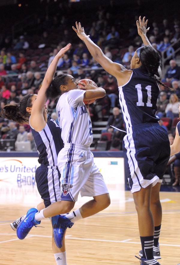 The University of Maine's Cherrish Wallace (center) goes up for a shot between Yale University's Zenab Keita (right) and Sarah Halejian during their game at the Cross Insurance Center in Bangor Sunday.
