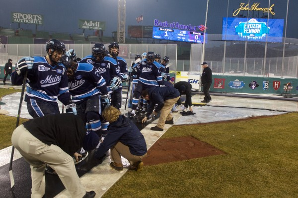 University of Maine players leave the ice as the game at Frozen Fenway is halted due to rain, thunder and lightning on Saturday.