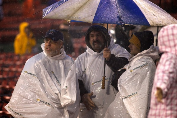 University of Maine Hockey fans gather under an umbrella as the game at Frozen Fenway is halted due to rain, thunder and lightning on Saturday.