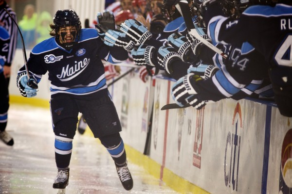 University of Maine's Ryan Lomberg celebrates after scoring a goal in the first period of a hockey game Saturday against Boston University at Frozen Fenway just before a rain delay was called.