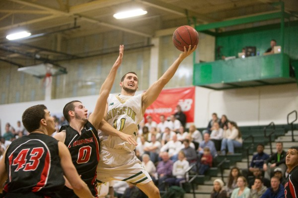 Husson University's Phil Leighton puts up a shot over a Thomas College defender on Dec. 3, in Bangor.