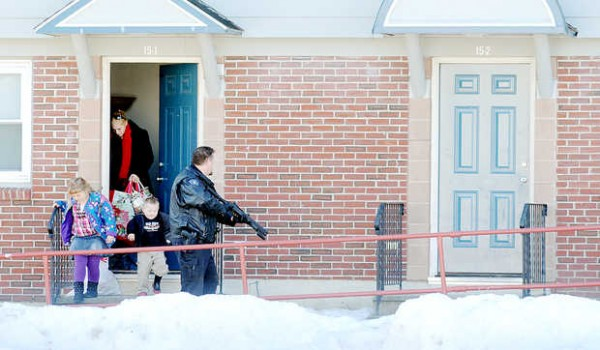 Neighbors leave their apartment as a Lewiston police officer trains his weapon at unit 2 in Building 15 on Cole Street on Monday.